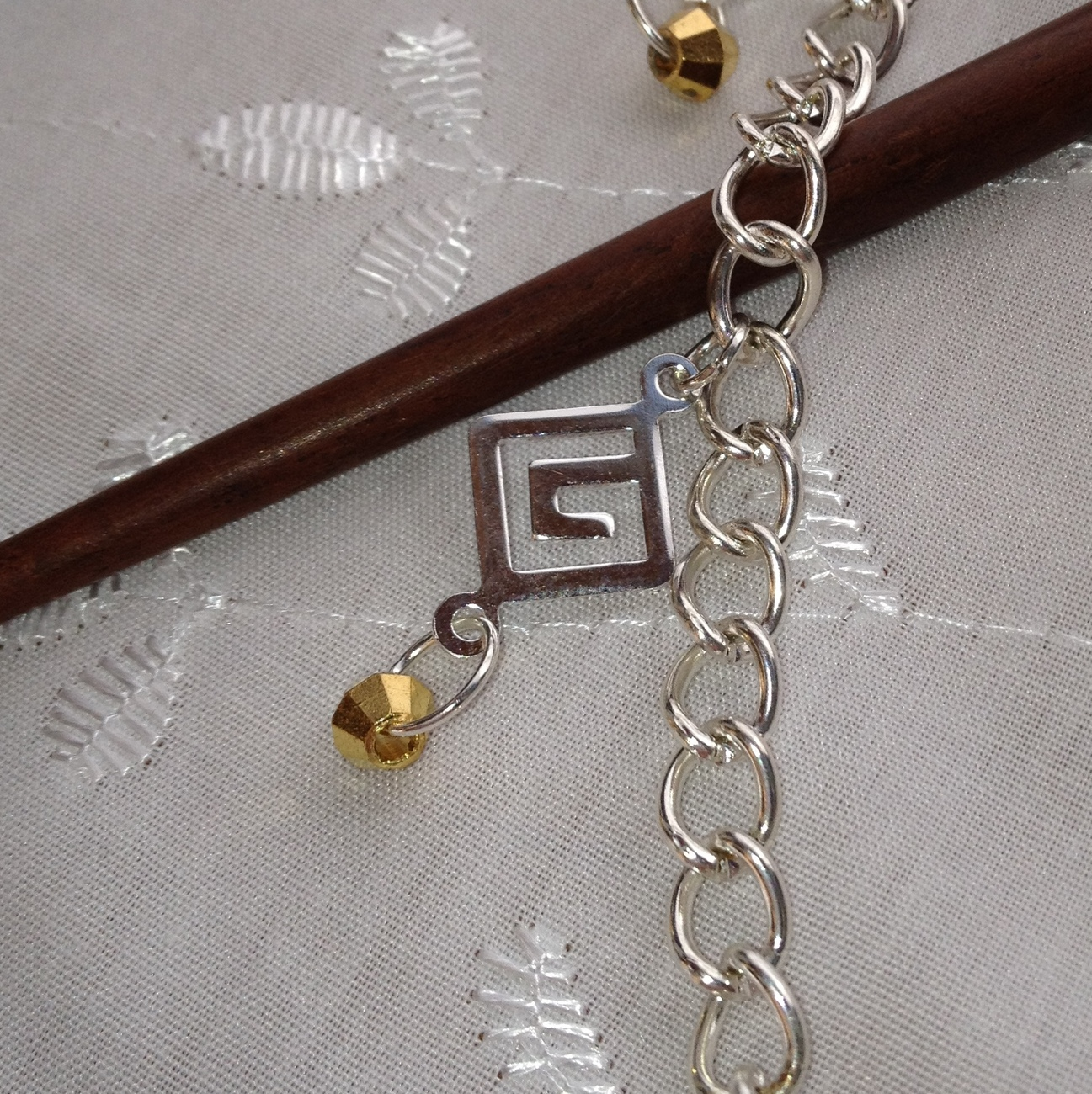 Pair of rosewood hair sticks linked by silvertone chain with charm dangles